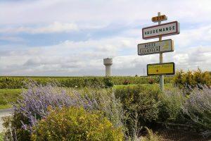 Photographie : Extérieur jour : entrée du village de vaudemange. Textes panneaux : Vaudemange, Route touristique du Champagne, Village fleuri *
