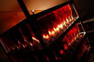 Photographie, intérieur. Un ensemble de bouteilles de champagne rosé est rangé dans un cube ouvert. L'ambiance est sombre et un projecteur fait ressortir la couleur des bouteilles qui illumine la pièce