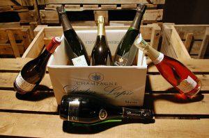 Photographie. Intérieur. Les 6 bouteilles de Champagne contenues dans le coffret découverte présentée dans le carton. Bouteilles : Prestige, Blanc de blancs, Blanc de noirs, Vieilles vignes 2009, perle fruitee (rosé), ratafia