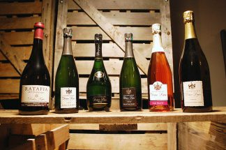 Photographie. Intérieur. Les 6 bouteilles de Champagne contenues dans le coffret découverte sont en présentation : Prestige, Blanc de blancs, Blanc de noirs, Vieilles vignes 2009, perle fruitee (rosé), ratafia