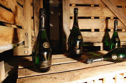 Photographie, intérieur. Plusieurs bouteilles de champagne de la cuvée Prestige sont disposées dans un décor ambiance cave