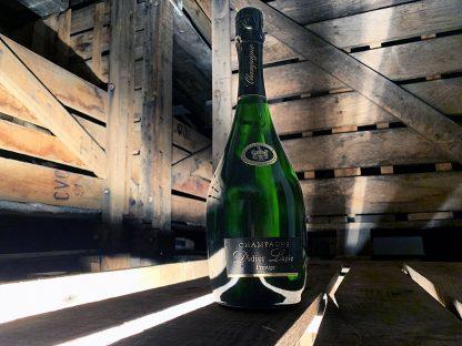 Photographie, intérieur. Une bouteille de champagne de la cuvée Prestige est mise en avant dans un décor ambiance cave. Texte étiquette : Champagne Didier Lapie Prestige