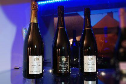 Photographie, intérieur. 3 bouteilles de champagne sont présentées. Textes étiquettes : Vieilles vignes 2009, Blanc de noirs, Blanc de blancs. Champagne Didier Lapie, viticulteur à vaudemange.