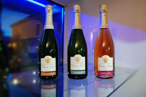 Photographie, intérieur. 3 bouteilles de champagnes sont présentées. Texte etiquettes : Perle de douceur, perle brute, perle fruitée. Champagne Didier Lapie, Viticulteur à Vaudemange