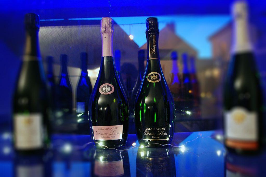 Photographie, intérieur. 2 bouteilles de champagne de forme particulière (plus bombée) sont présentées. Textes étiquettes : Prestige ; Ephémère rosé. Champagne Didier Lapie, Viticulteur à Vaudemange.