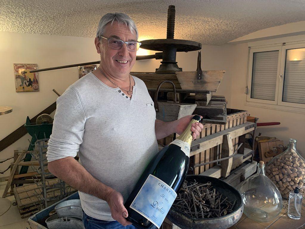 Portrait de Didier Lapie, qui tient une bouteille de champagne, devant un ancien pressoir