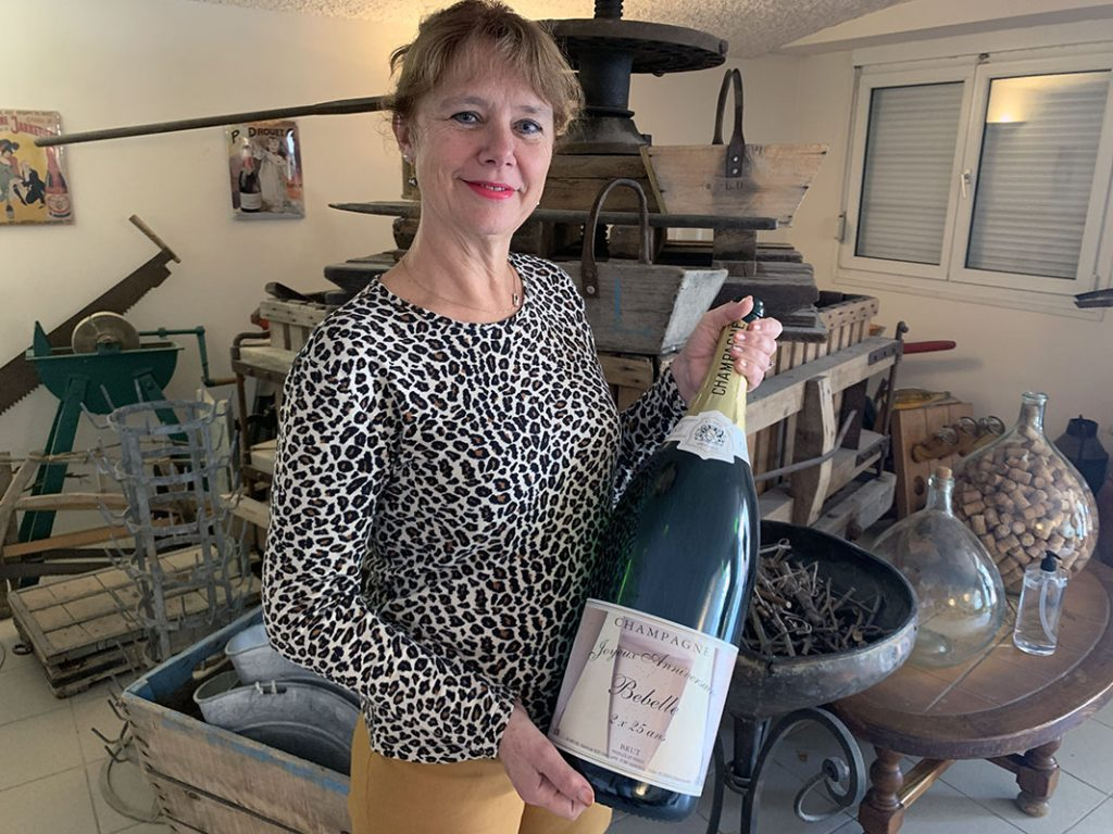 Portrait de Isabelle Lapie, qui tient une bouteille de champagne, devant un ancien pressoir
