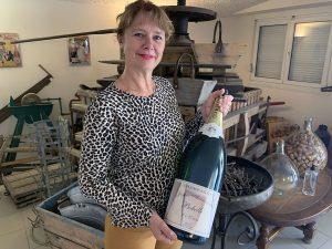 Photographie : Portrait de Isabelle Lapie dans la boutique, tenant un bouteille de Champagne