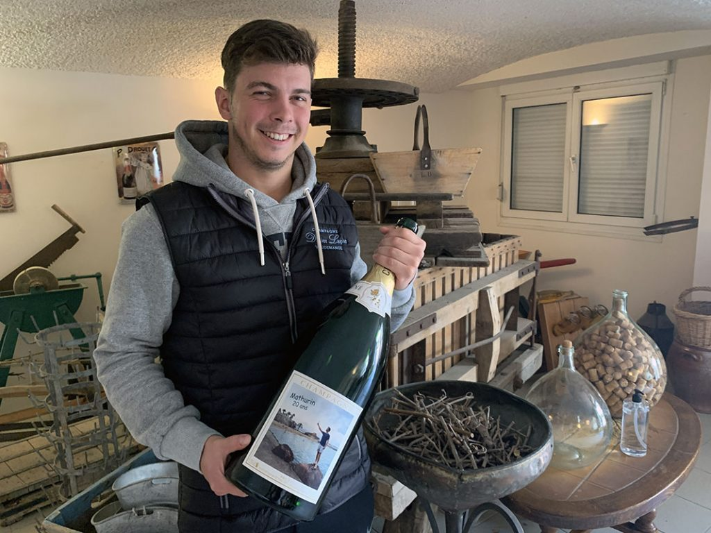 Portrait de Mathurin Lapie, qui tient une bouteille de champagne, devant un ancien pressoir