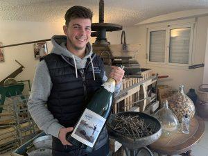 Photographie : Portrait de Mathurin Lapie dans la boutique, tenant un bouteille de Champagne