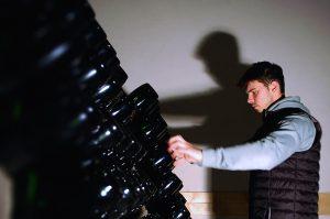 Photographie, intérieur. Mathurin Lapie est devant un présentoir de bouteilles de champagne inclinées vers le bas, et est en train de les tourner, ce qui fait parti du processus de vinification