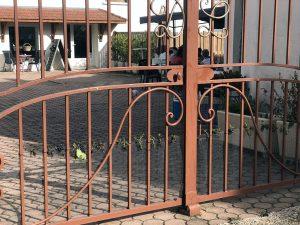 Extérieur jour. Photographie d'un portail de couleur cuivre, donnant sur une cour intérieur. Au second plan se trouve une table ou des clients sont (bien ;)) reçus. En arrière plan la boutique, avec un présentoir à bouteilles en extérieur.