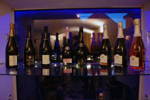 Photographie, intérieur. L'ensemble des cuvées Champagne Didier Lapie : toutes les bouteilles sur une étagère en verre