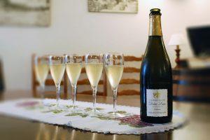 Photographie, intérieur. Une bouteille de champagne est débouchée, et à côté sont servies 5 flûtes de champagne. Texte étiquette de la bouteille : Vieilles vignes 2009